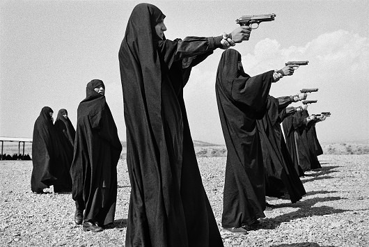IRAN. Tehran. 1986. Veiled women practice shooting on the outskirts of the city.